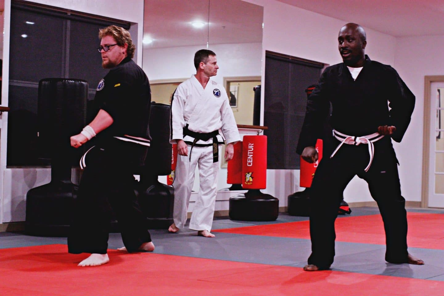 adult taekwondo students practicing forms with instructor in the background