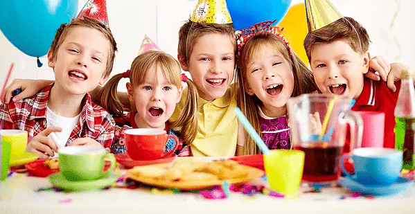 Kids celebrating a birthday party with party hats on