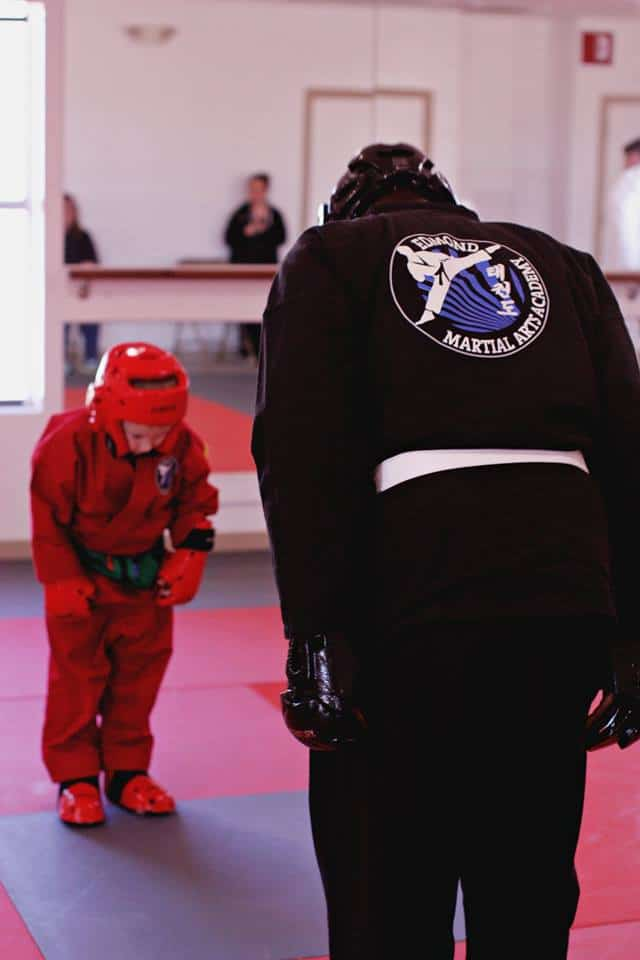 instructor and young student bowing to each other before sparring