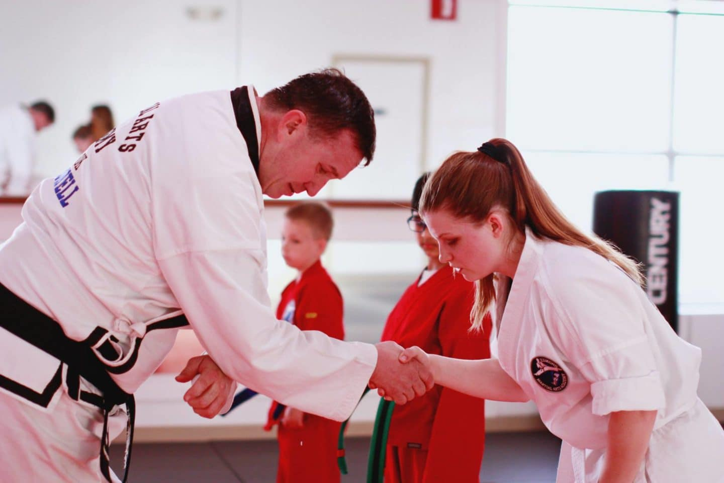 instructor shaking hands with youth student in white uniform