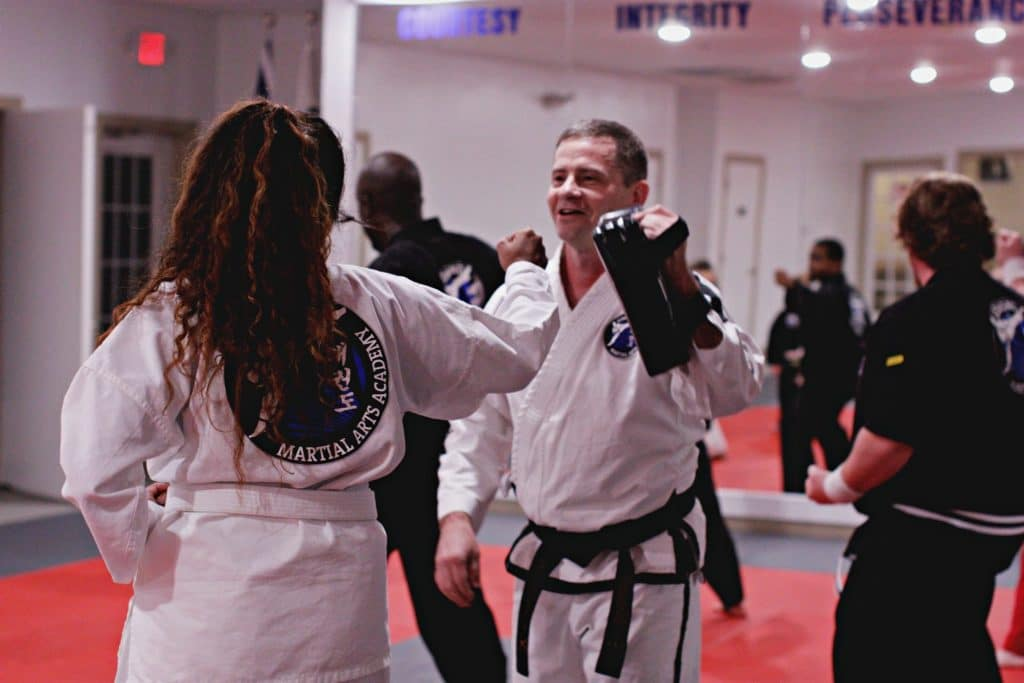 adult taekwondo student practicing hitting technique on hand training pads