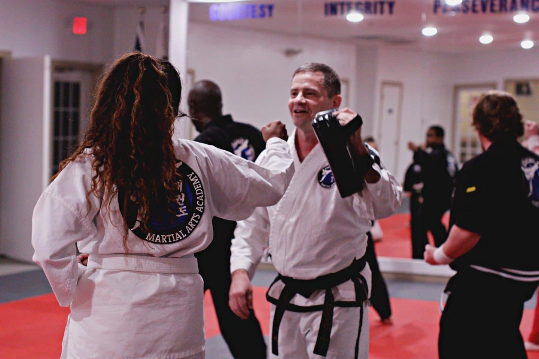 adult taekwondo student practicing hitting technique on hand training pads
