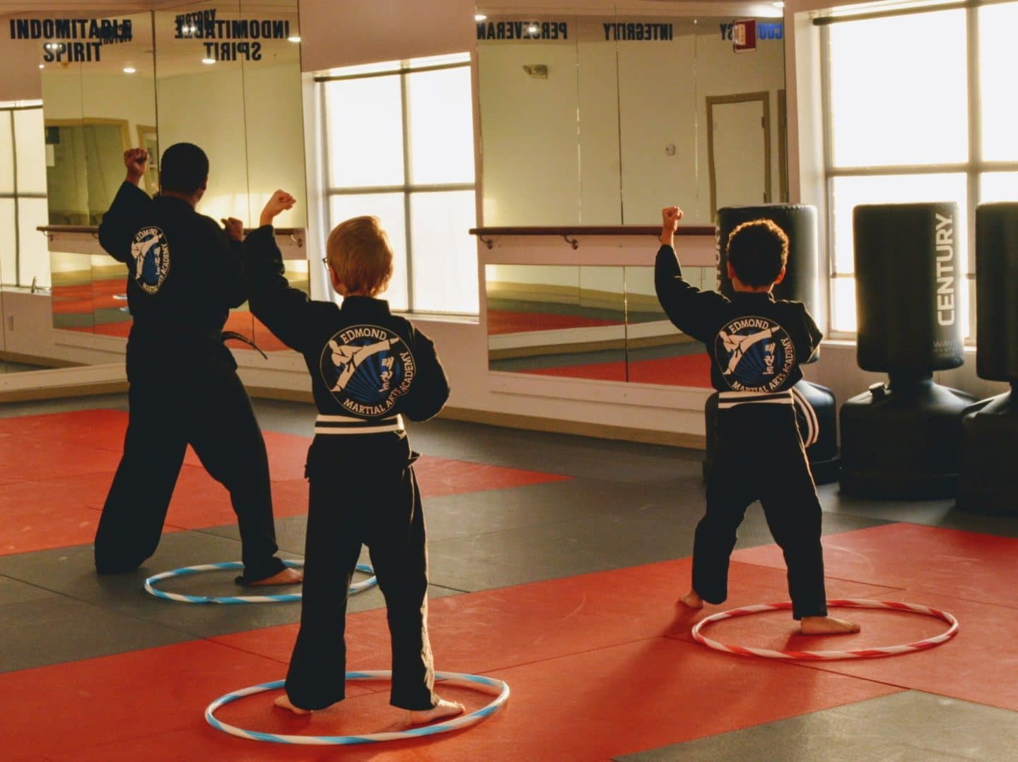 young taekwondo students practicing forms based on instructor's demonstration