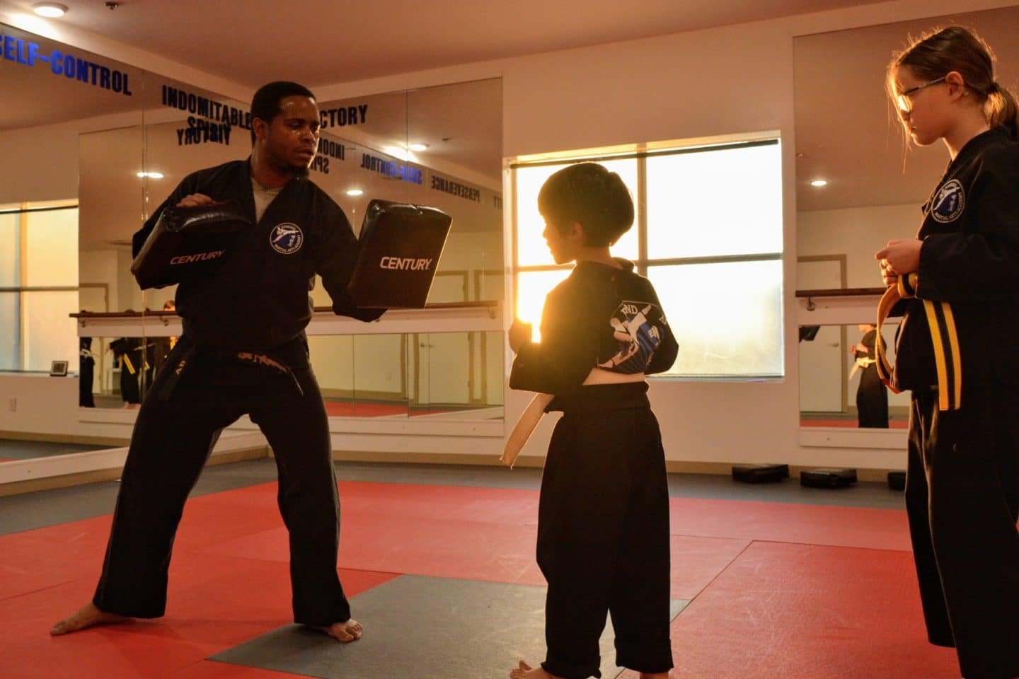 youth student practicing hitting training target pads being held by instructor