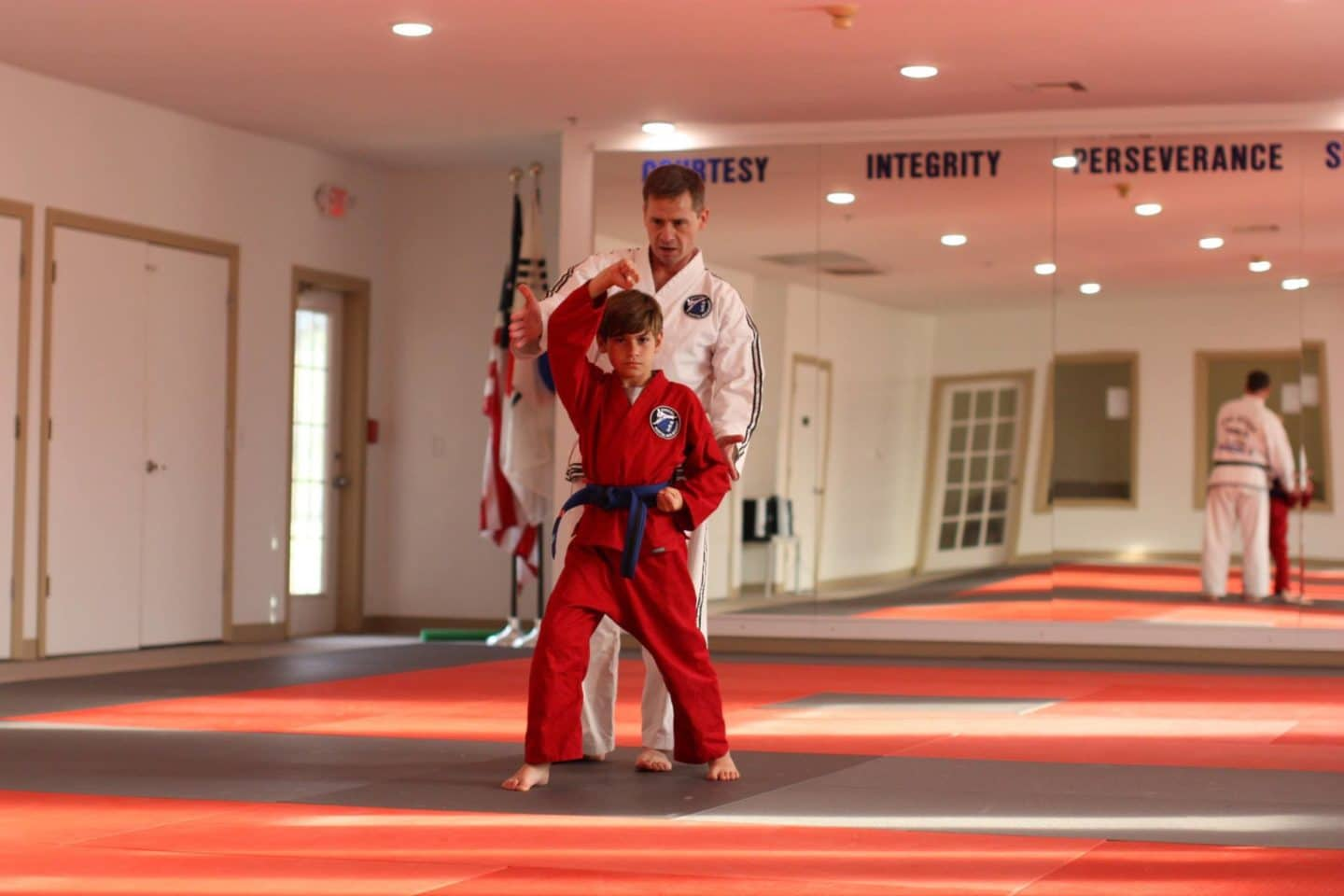 young student with instructor correcting taekwondo forms