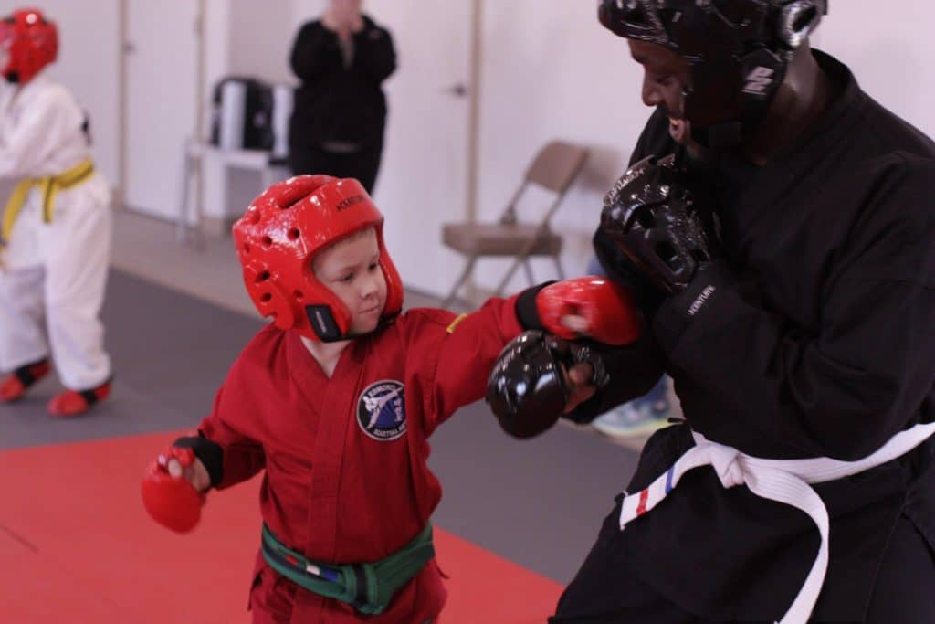 very young student practicing sparring with instructor
