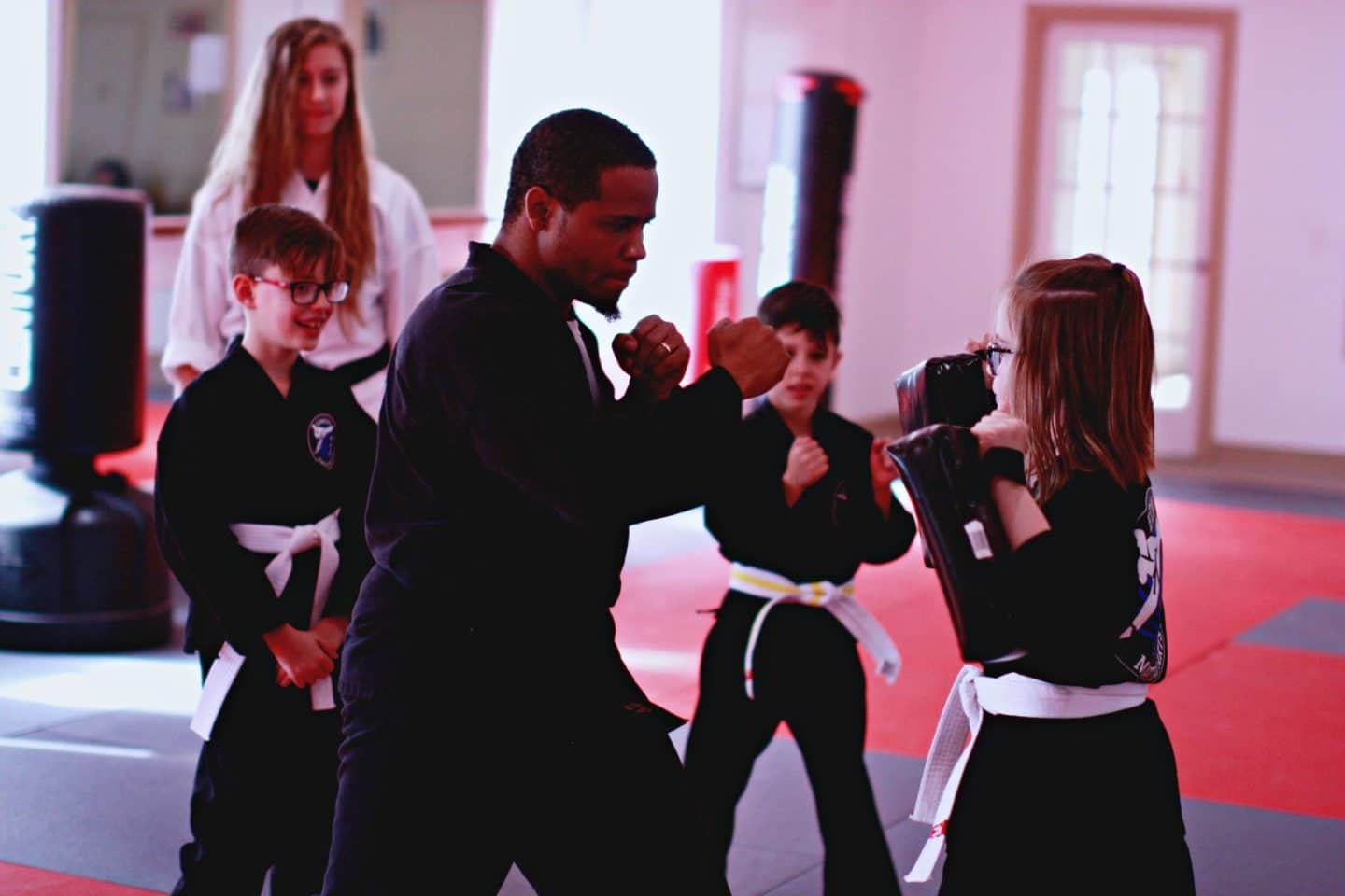 instructor showing proper striking technique to young students