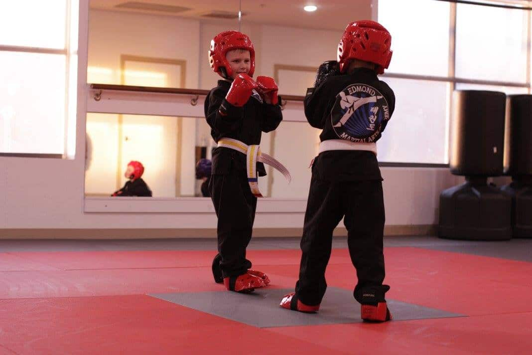two youth students practicing sparring each other