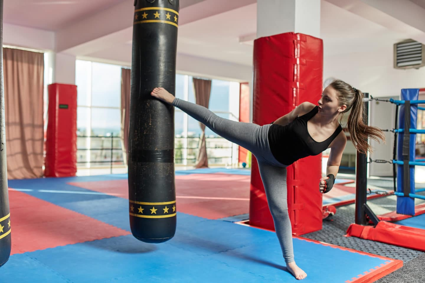 Muay thai female fighter training with the heavy bag